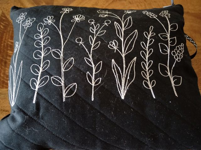Image of a black quilted zipper bag with white flowers embroidered on it.
