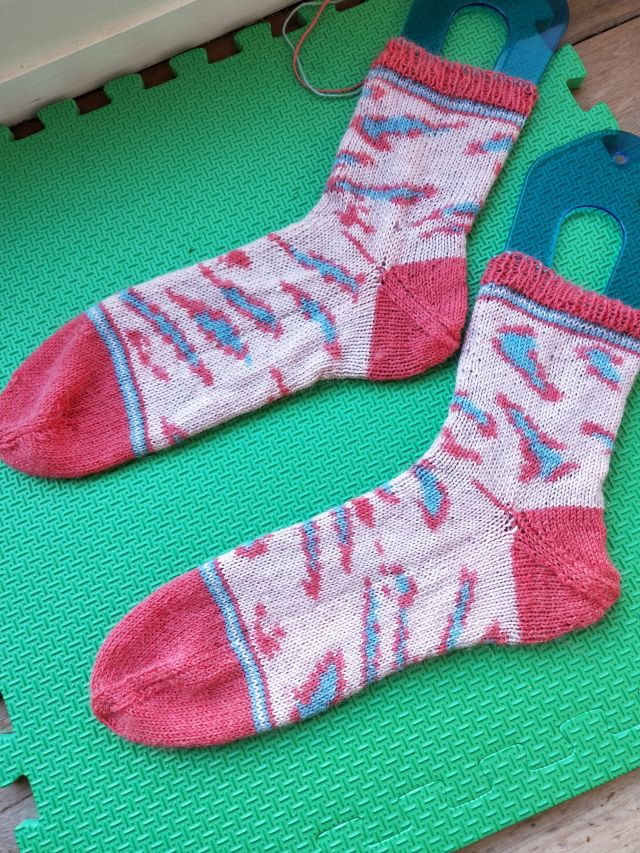 Image of Wool and the Gang's Kinda Magic socks - socks with a light pink ground with blue and darker print leopard spots and darker pink toes and heels